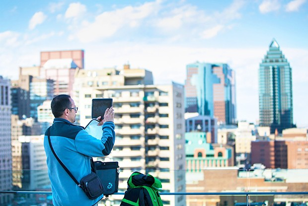 A congress-goer ponders Montreal's magnificent skyline from the terrace of the Engineering, Computer Science and Visual Arts Integrated Complex (EV Building). | Photo by Hombeline Dumas