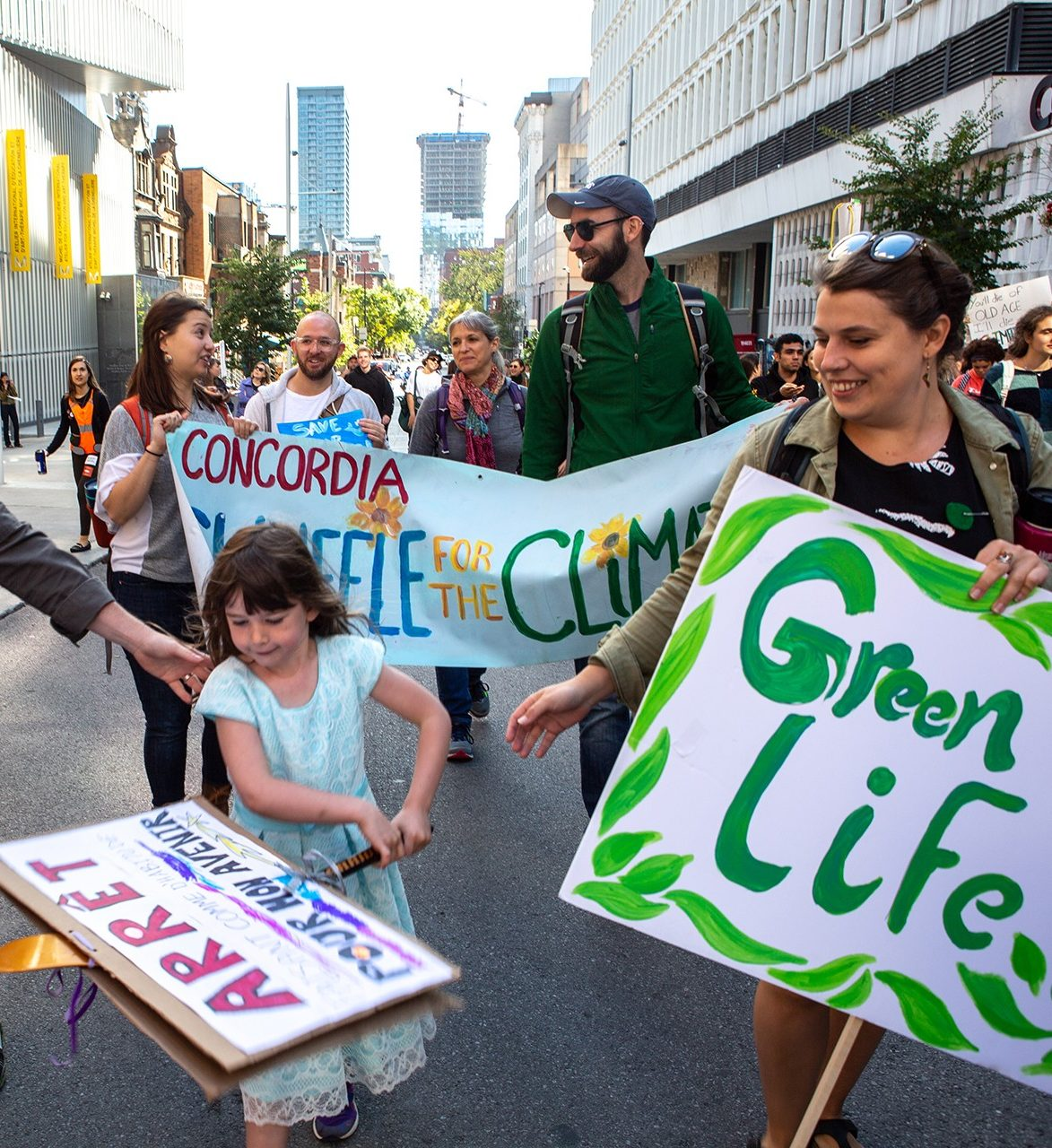 people holding signs participate in a climate march walking past Concordia's downtown campus