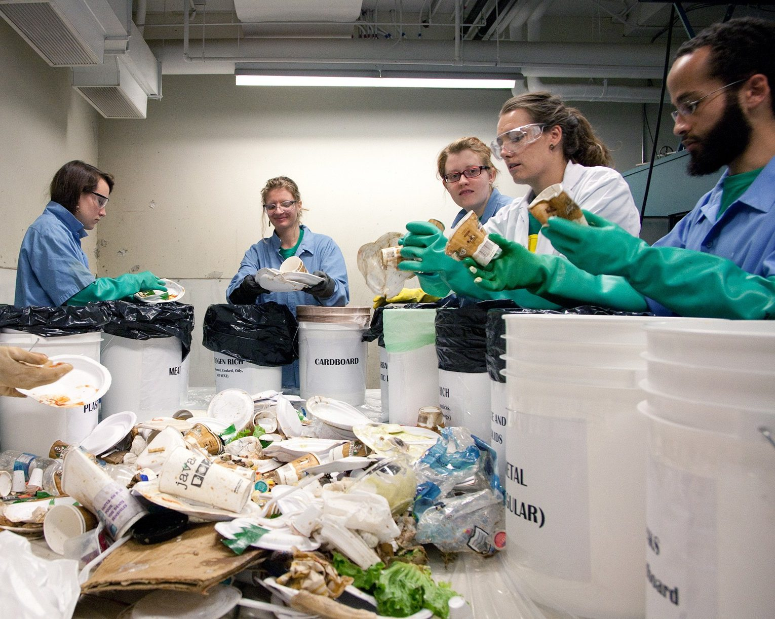 a group of people in lab coats and gloves sorting waste for recycling