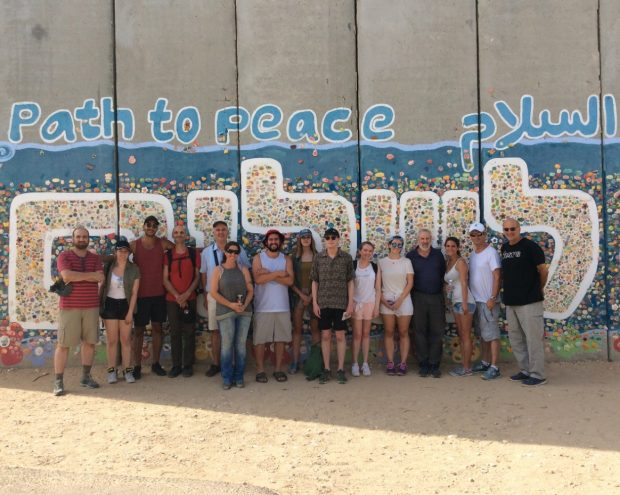 Participants stand in front of a painted mural in Israel