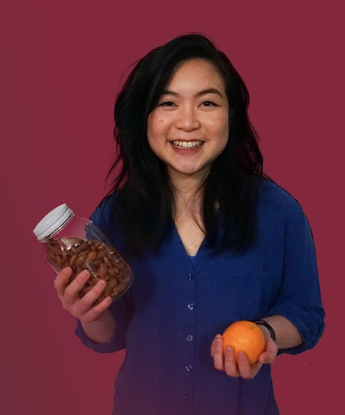 Dietitian Jessy Cheung holds a bottle of almonds and an orange
