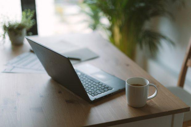 An open Laptop computer and a cup of coffee on a table