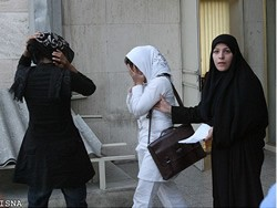 Morality Police officer apprehending two women in the streets of Tehran for wearing improper hijab.