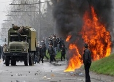 Kyrgyz opposition supporters attack a riot police vehicle during an anti government protest in Bishkek on April 7, 2010. Credit: Vyacheslav Oseledko, AFP, Getty Images