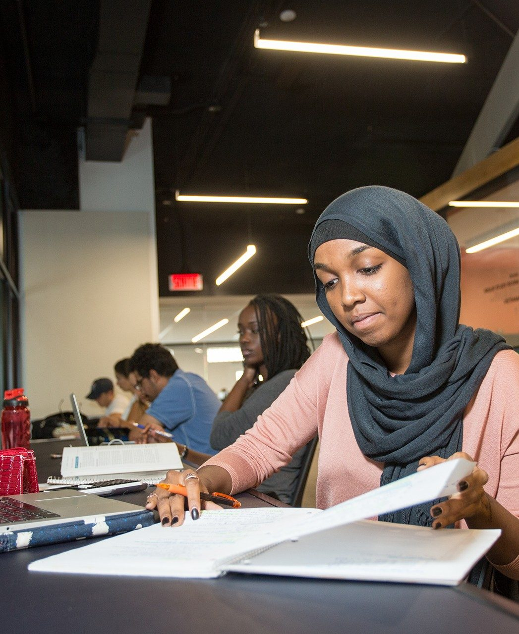 A student wearing a hijab reads a page in a notebook and other students study nearby