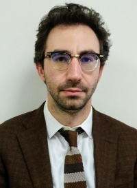 Headshot of man wearing suit and glasses.
