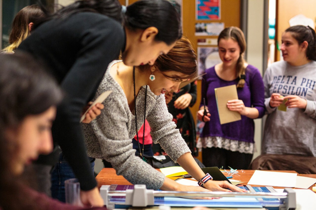A Sustainability Ambassador is surrounded by students. Everyone is looking down at what is on the table, which is not clear by the camera angle.