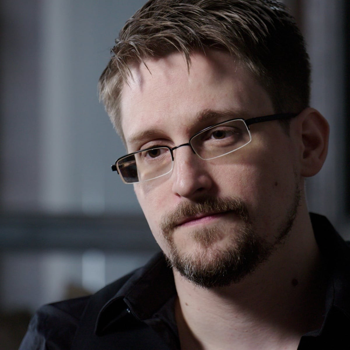 Headshot of Edward Snowden from shoulders up. White man with short-cropped brown hair, wireframe glasses and goatee. Wearing black, button-up shirt.