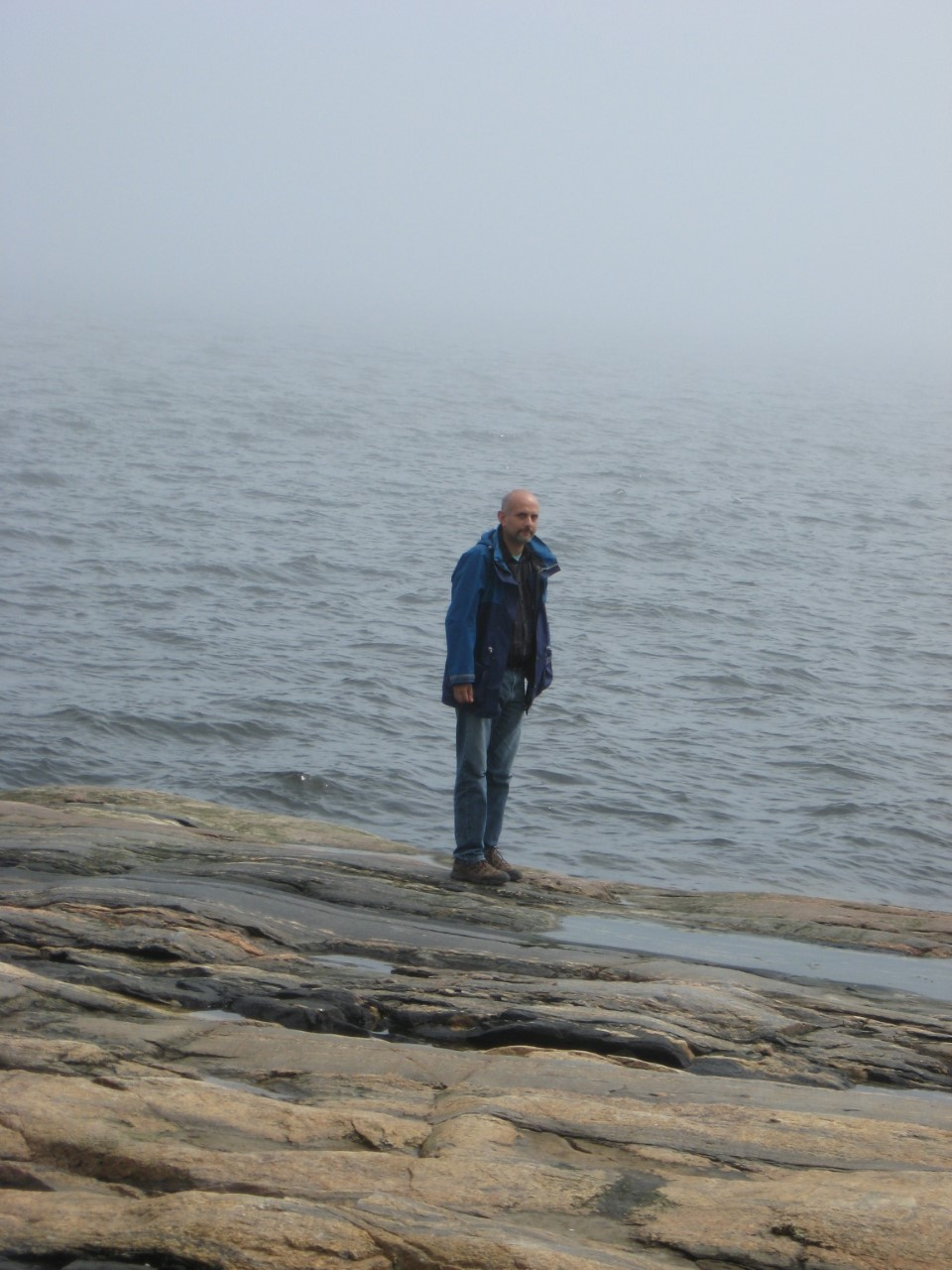 Aziz Choudry stands on a rocky beach with a large body of water behind him. He wears a dark blue rain coat and blue jeans.