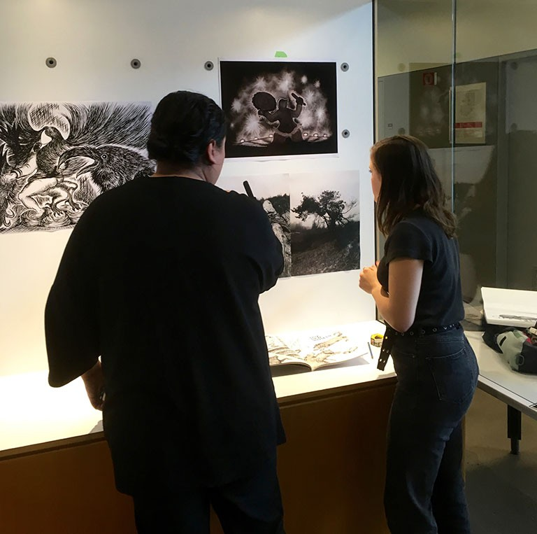Co-curators Hanss Lujan Torres (left) and Renatta Critton-Papp (right) install the work of BFA candidate Jason Sikoak at Concordia's Art History Vitrine, one of four locations for the exhibition series Waterways: Asian Indigenous Relations in Contemporary Art.
