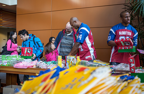 Hebert and Chima Ihekwoaba, defensive end for the Alouettes, explain how the charity works to passersby.