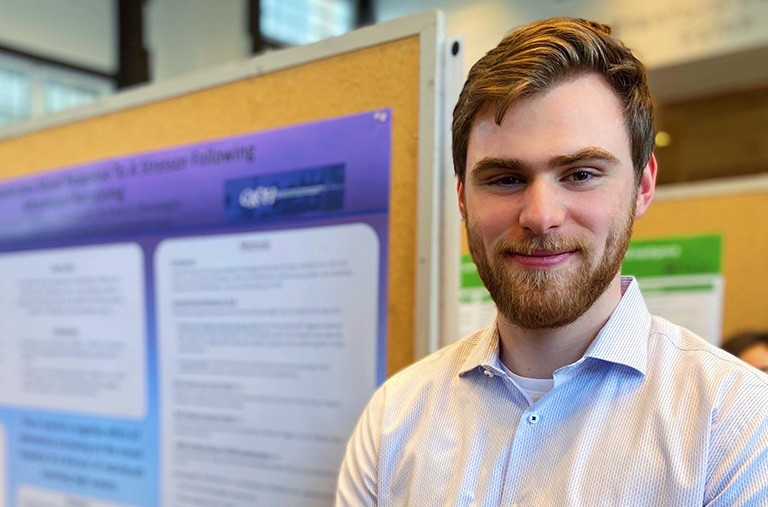 Young man with blonde hair, a beard and a white shirt, standing in front of a presentation board.