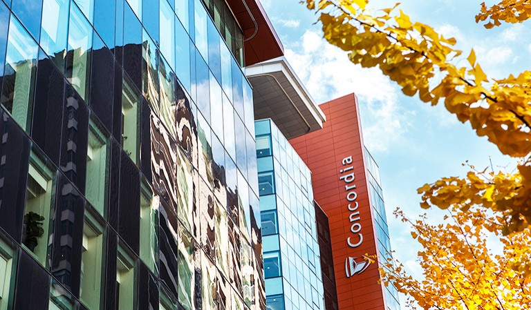Shot of buildings from below, with the Concordia University logo down the side of one, and autumn leaves on the right of the picture.