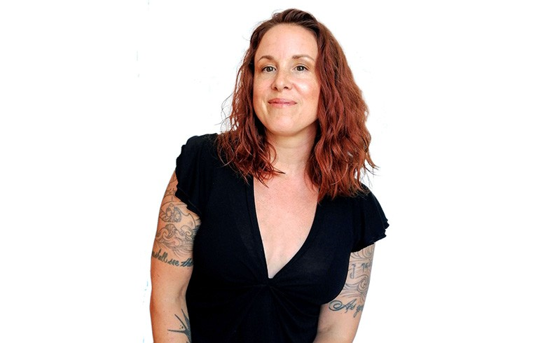 Women with red hair and arm tattoos, dressed in a black shortsleeved t-shirt.