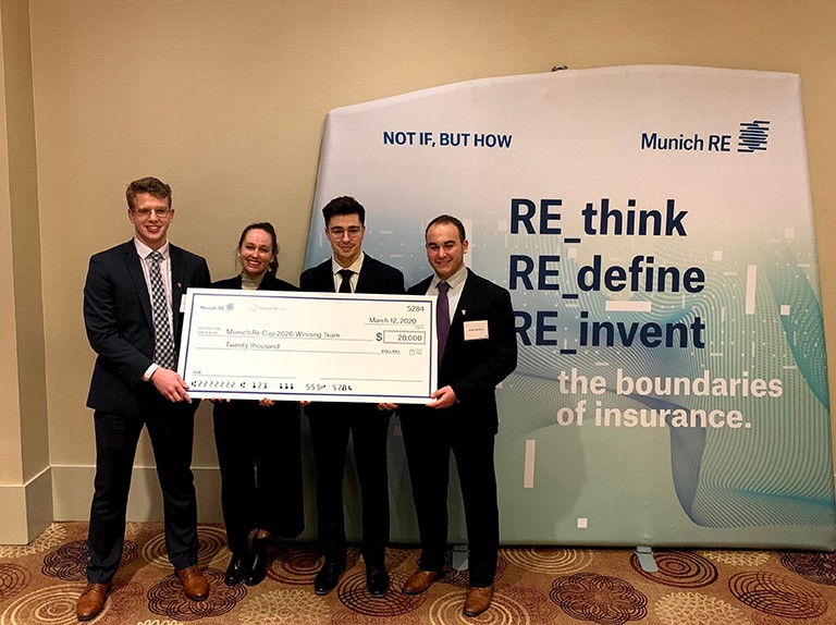 Four Concordia students in formal attire holding a big cheque in front of a Munich RE banner.