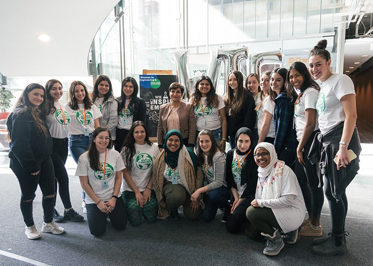 Group of young women gathered together and smiling for the camera in an atrium space.