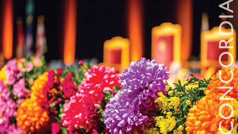 Bunches of colourful flowers in the foreground, with a stage in the background.