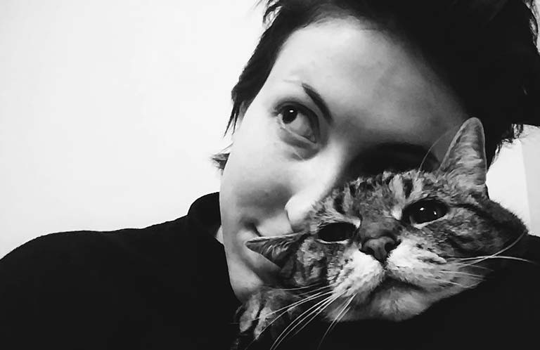 Young woman with short, dark hair cuddling a tabbie cat.