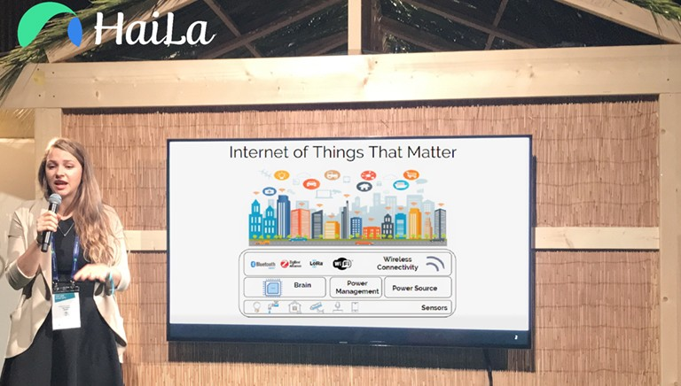 Young, blonde woman giving a presentation with a microphone and a board in the background that says, 'Internet of things that matter.""