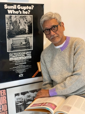 portrait of Sunil Gupta siting beside a poster from a 1983 exhibition of his work.