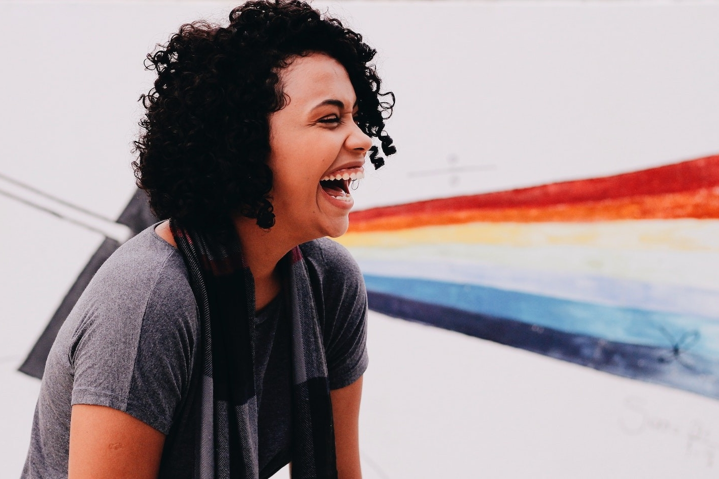 A woman laughs in front of a colourful mural