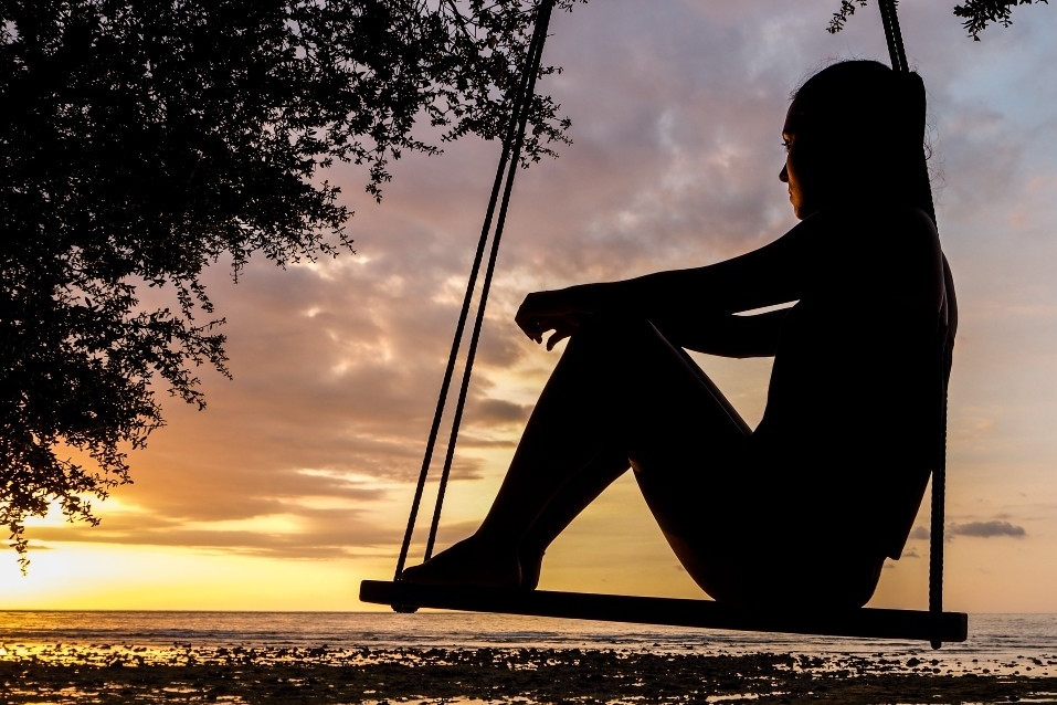 Silhouette of a woman on a swing looking at the sunset