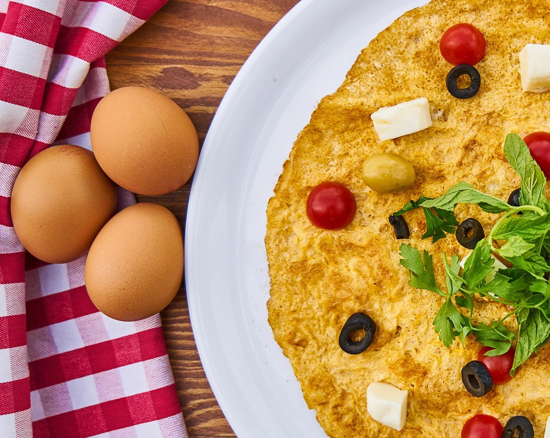 A healthy omelette with olives and greens