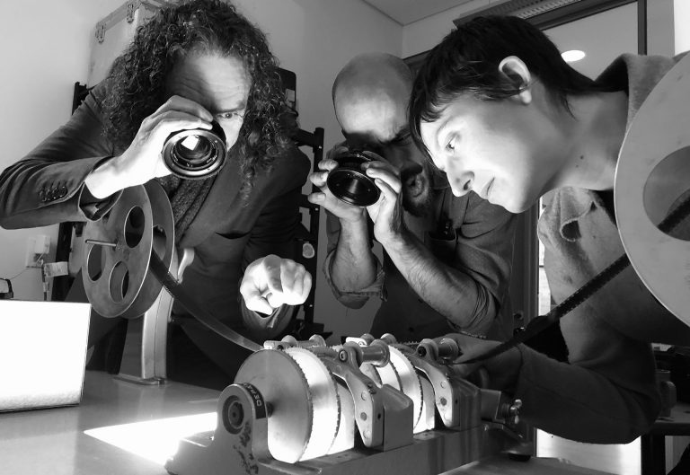 Devotees of emulsion Roy Cross, Kevin Teixeira and Erin Weisgerber undertake close inspection of film processed in instant coffee. | Photo by Daisy Woodhams