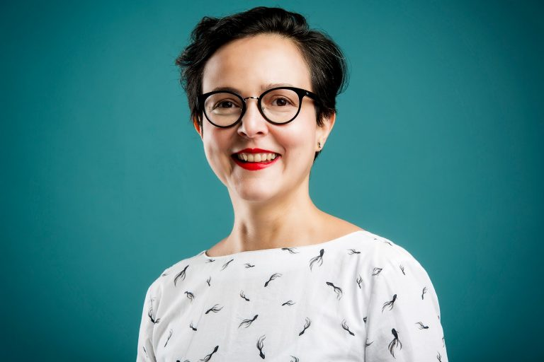 A light-skinned woman with dark short hair and glasses, wearing a white patterned shirt, red lipstick and smiling against a dark turquoise background.