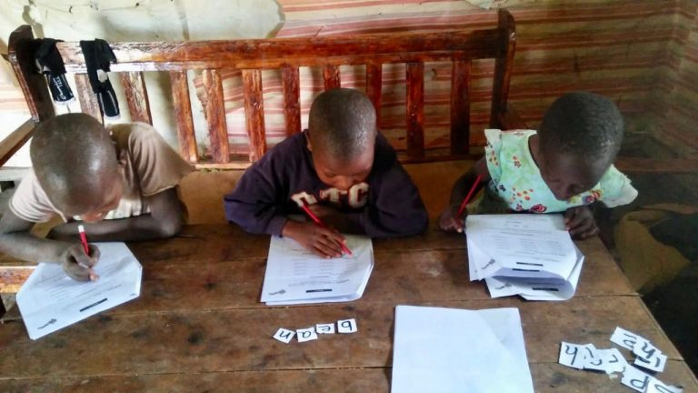 Three children from the Trans Mara region of Kenya sit at a desk doing their schoolwork.