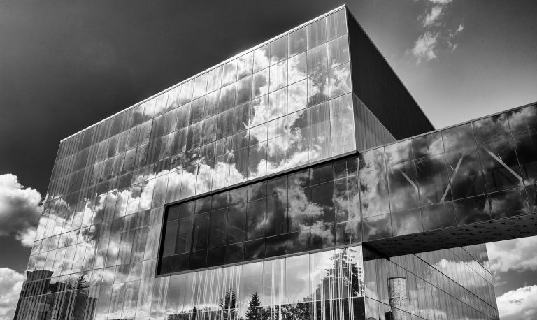 Image in black and white of a building made of glass, with a glass tunnel stretching from the building to beyond the edge of the photo.