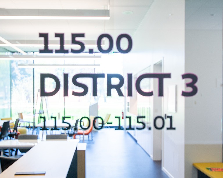 "Blurry view through a window with the words ""155.00, District 3, 115.00-115.01"" on the glass, into a classroom."