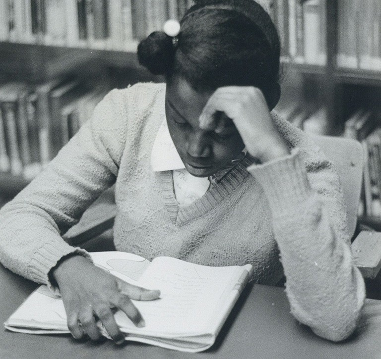 Girl reading at a table in front of a bookshelf, probably at the library in the Negro Community Centre. | Photo: Graeme Clyke