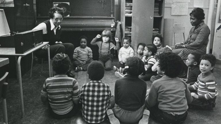 An archive image of a classroom with two teachers and several children sitting in a circle.