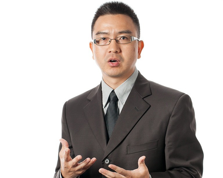 A young man with short dark hair, of asian heritage, wearing steel-rimmed glasses and a brown suit.