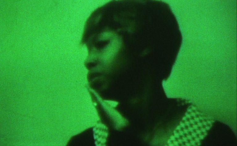 A black woman with short hair, her hand to her face, with a green-wash tint to the image.