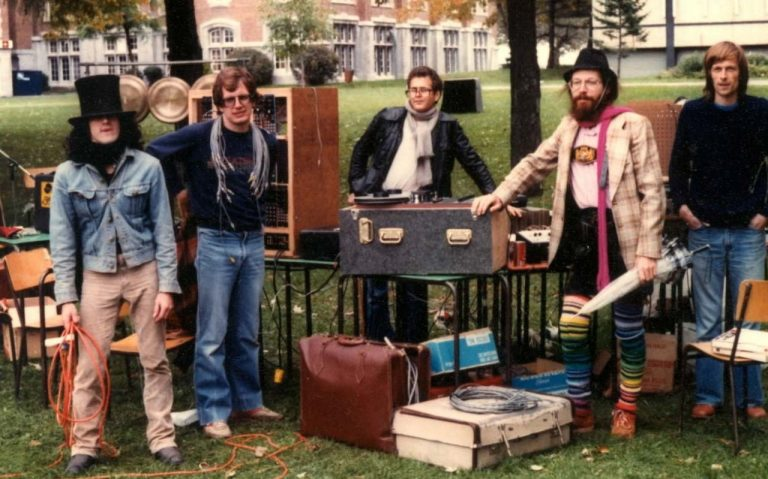 An archive photo c. 1982 of a group of musicians on a university lawn, with all their instruments