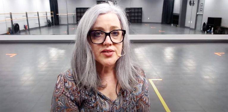 On older woman with long grey hair and glasses, talking into a headpiece.