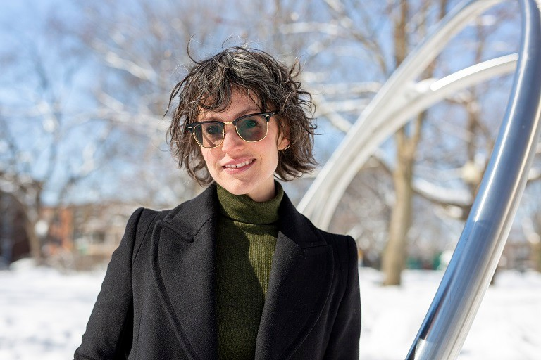 Young woman outside with sunglasses on a sunny winter day